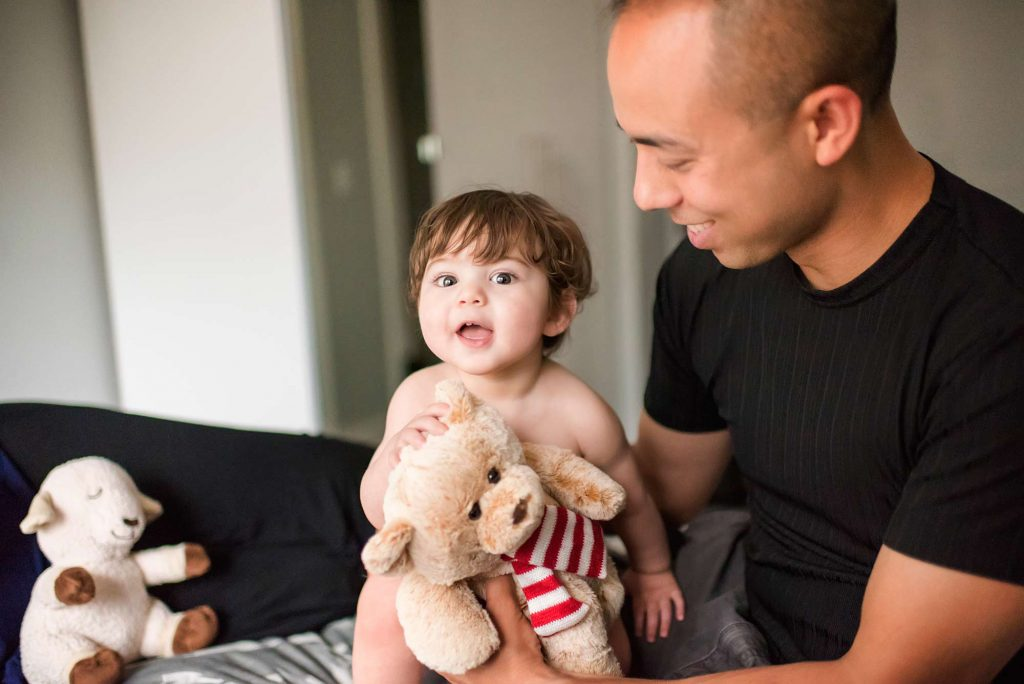 Toddler with teddy bear and father