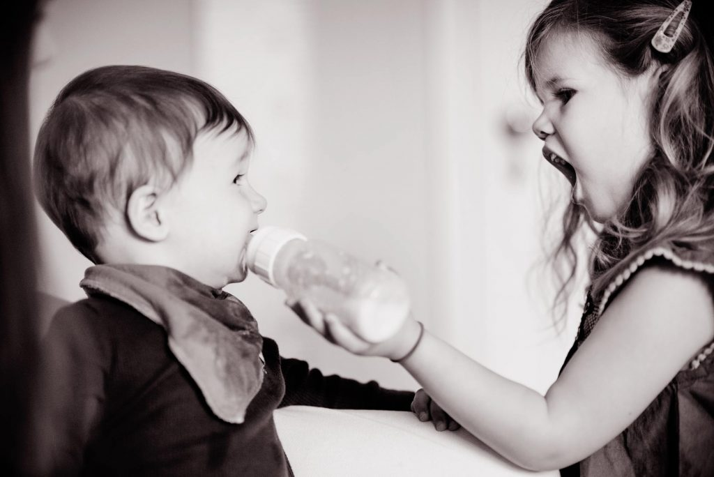 Sister feeding little brother with bottle