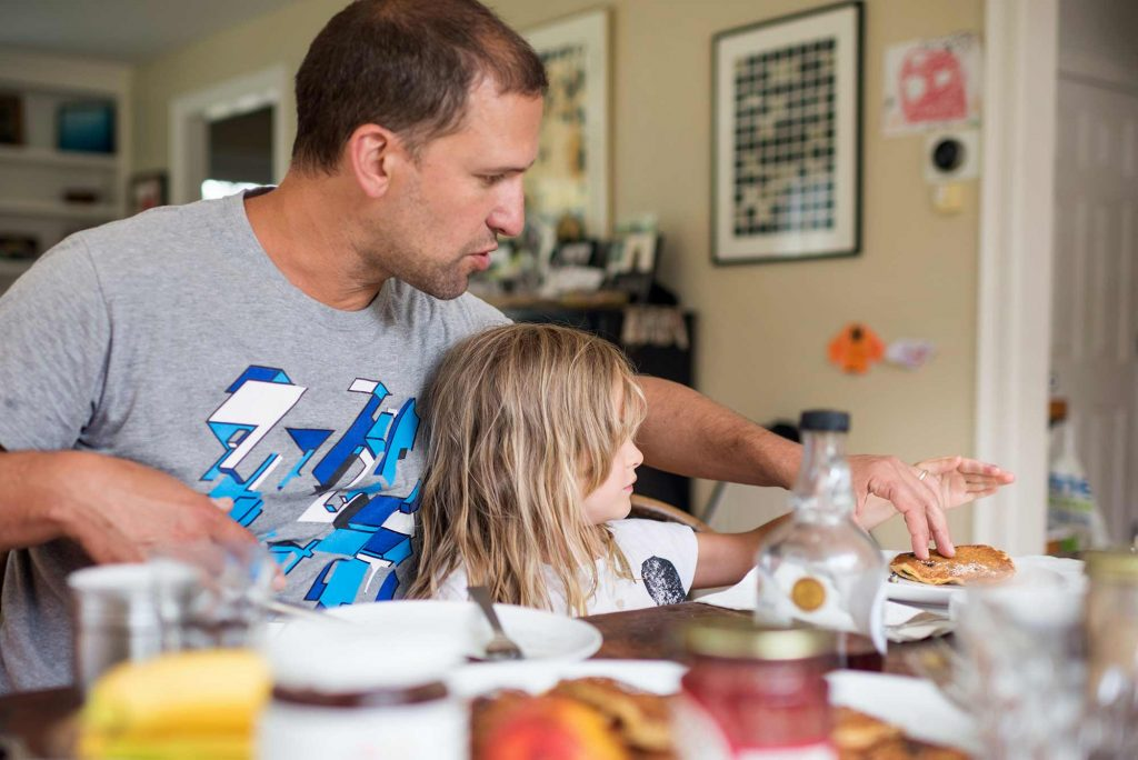 Father and daughter eating pancakes